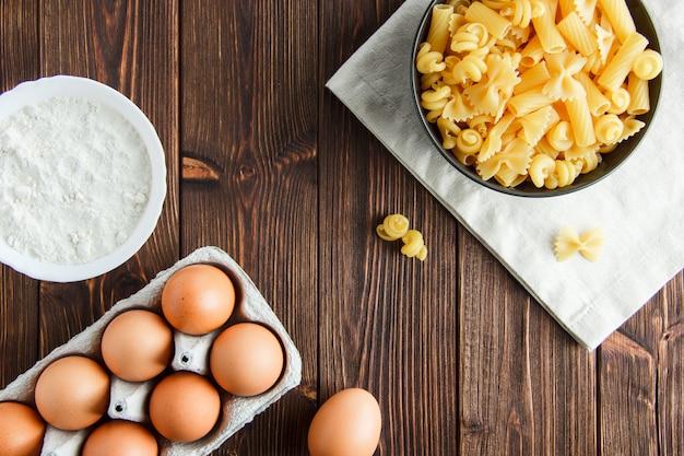 Macarrão cru em uma tigela com ovos, farinha plana colocar em madeira e toalha de cozinha