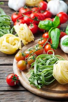 Macarrão cru, tomate e manjericão na mesa de madeira