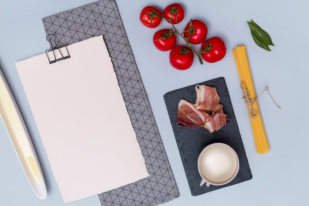 Macarrão cru; tomates; carne; molho branco; folhas de louro e papel branco em branco com guardanapo no pano de fundo liso
