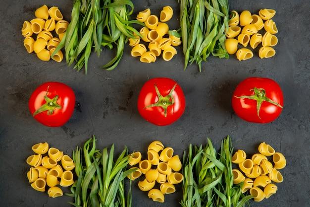 Macarrão cru top ditalini com tomates frescos e estragão no preto