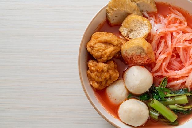 Macarrão de arroz achatado com bolinhos de peixe e bolinhos de camarão na sopa rosa, yen ta four ou yen ta fo. comida asiática