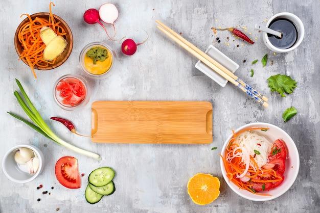 Macarrão de arroz asiático com legumes e salada vegetariana em um prato fundo de pedra