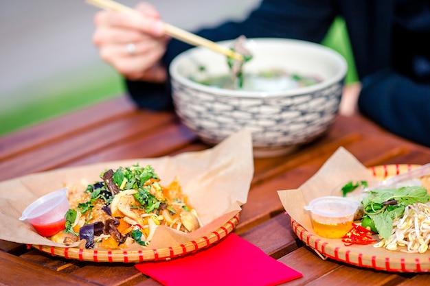 Macarrão de arroz asiático com legumes e sause close-up em cima da mesa