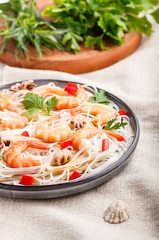 Macarrão de arroz com camarão ou camarão e polvos pequenos na placa cerâmica cinza em um foco seletivo de têxteis de linho branco