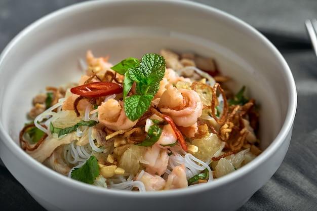 Macarrão de arroz com camarões e frutos do mar, macarrão picante de estilo asiático na tigela