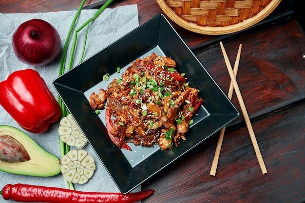 Macarrão de arroz com milho bebê, pimentão, cebola, cenoura e frango frito em um wok com molho teriyaki em chapa preta na mesa de madeira. saborosa comida de rua asiática