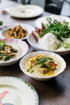 Macarrão de arroz com molho de caril de carne de caranguejo, servido com legumes.