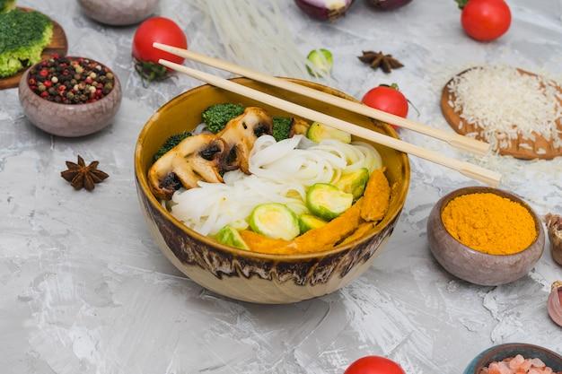 Macarrão de arroz cozido; cogumelo; couve de bruxelas e frango frito na tigela com pauzinhos sobre superfície texturizada de cimento