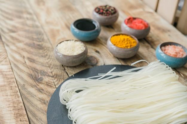 Macarrão de arroz cru branco fresco sobre a pedra ardósia com especiarias na mesa de madeira