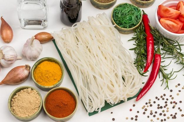 Macarrão de arroz e especiarias secas em tigelas verdes. cebola, raminhos de alecrim. molho de soja em garrafa de vidro. vista do topo.