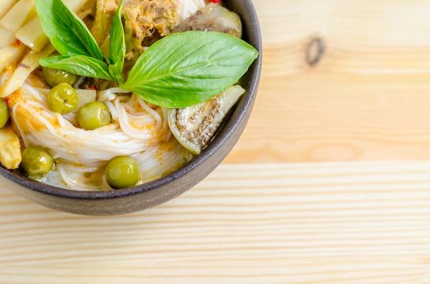Macarrão de arroz em molho de caril de frango com legumes em fundo de madeira