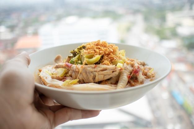 Macarrão de arroz em molho de caril de peixe com pés de galinha.