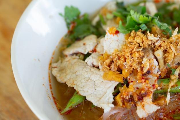 Macarrão de arroz em sopa picante com bola de carne de porco, legumes e carne de porco servindo na mesa de madeira na cantina