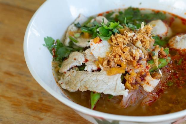 Macarrão de arroz em sopa picante com bola de porco, legumes e carne de porco servindo na mesa de madeira na cantina