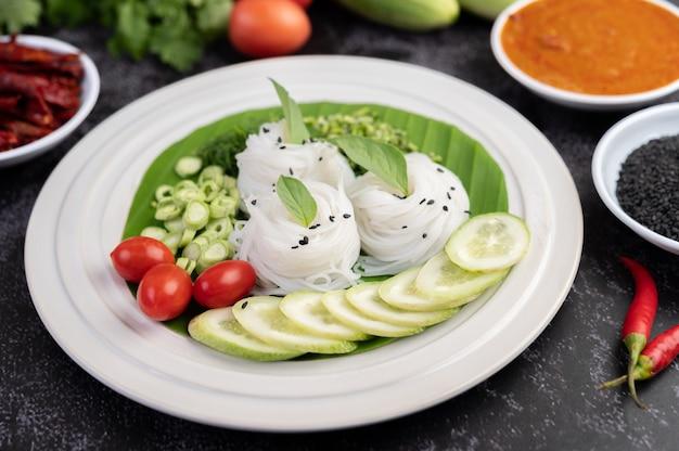 Macarrão de arroz em uma folha de bananeira com legumes e pratos maravilhosamente dispostos. comida tailandesa.