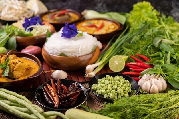 Macarrão de arroz em uma tigela de pasta de curry com pimenta, pepino, feijão comprido, limão, alho e cebolinha