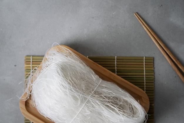 Macarrão de arroz fino cru no prato de bambu na superfície de pedra com varas