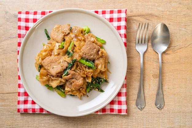 Macarrão de arroz frito com molho de soja preto e carne de porco e couve, estilo de comida asiática