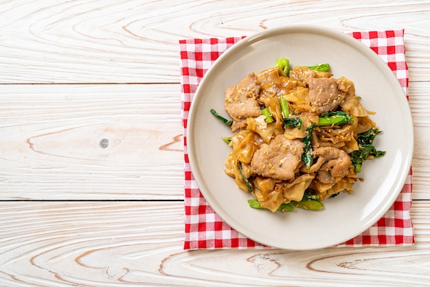 Macarrão de arroz frito com molho de soja preto e carne de porco e couve