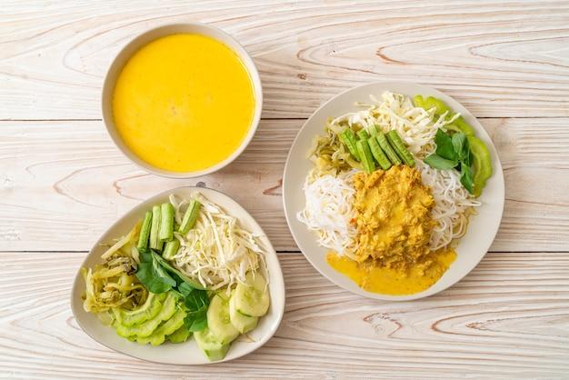 Macarrão de arroz tailandês com caril de caranguejo e vegetais variados