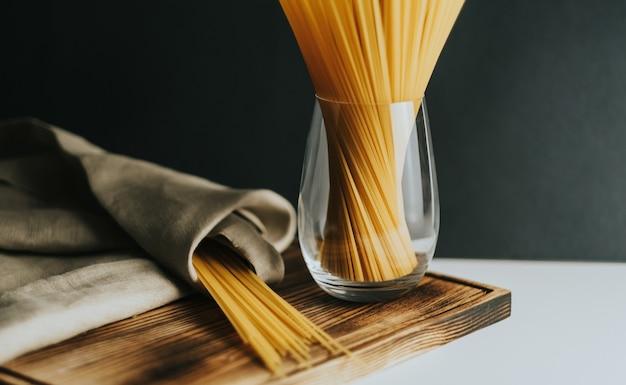 Macarrão de espaguete de trigo em vidro sobre uma placa de madeira