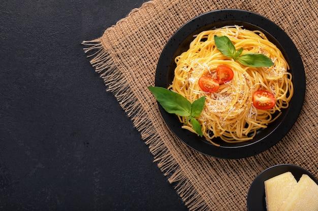 Macarrão de espaguete italiano clássico apetitoso vegetal vegetariano com manjericão, tomate e parmesão na chapa preta sobre uma mesa escura. vista superior, horizontal.