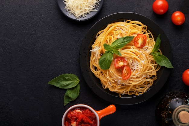 Macarrão de espaguete italiano clássico saboroso apetitoso com manjericão, molho de tomate, queijo parmesão e azeite no prato preto na mesa escura. ver os de cima, horizontal.