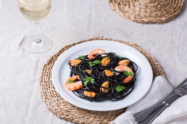Macarrão de espaguete preto com marisco camarão mexilhões e salsa