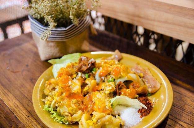 Macarrão de estilo tailandês na mesa de madeira e flor seca