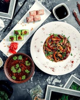 Macarrão de frango em cima da mesa com rolos de sushi