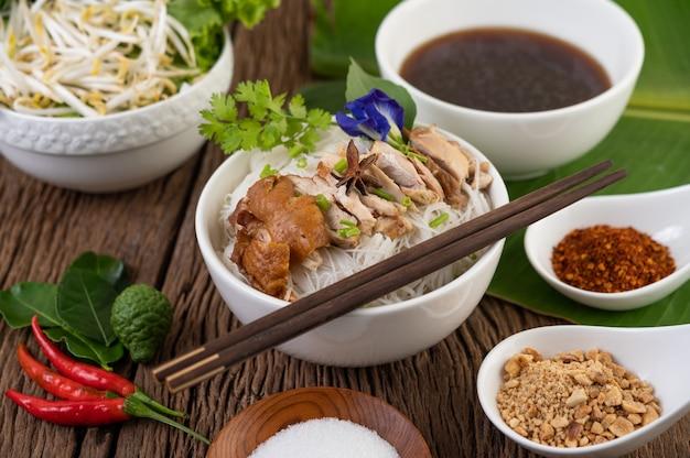 Macarrão de frango em uma tigela com acompanhamentos, comida tailandesa