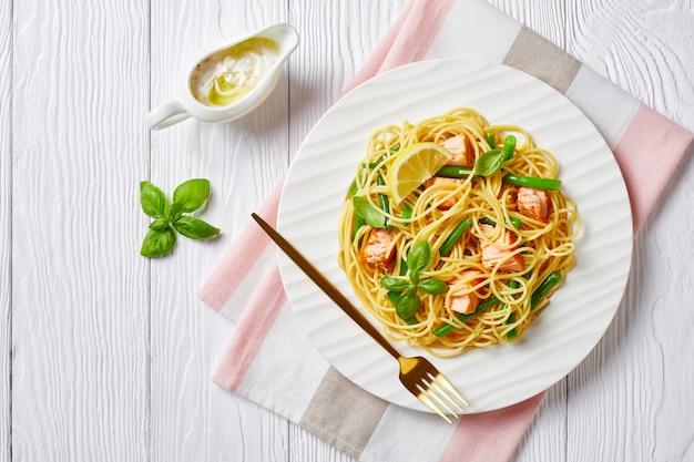 Macarrão de frutos do mar com salmão e feijão verde, espaguete italiano, com molho de manteiga de alho, manjericão fresco, limão servido em um prato branco com garfo em uma mesa de madeira branca, vista de cima, plano plano