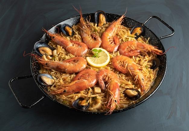 Macarrão de frutos do mar em mesa de madeira rústica - fideua