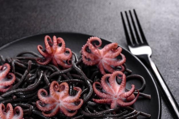 Macarrão de frutos do mar preto com camarão, polvo e mexilhões. comida gourmet mediterrânea. macarrão preto com polvo em uma placa de pedra preta