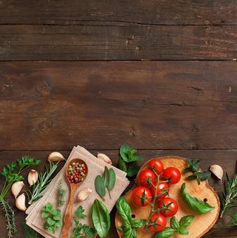 Macarrão de lasanha crua, vegetais e ervas em uma mesa de madeira
