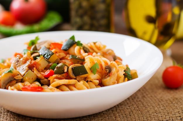 Macarrão de legumes vegetarianos fusilli com abobrinha, cogumelos e alcaparras em tigela branca na mesa de madeira