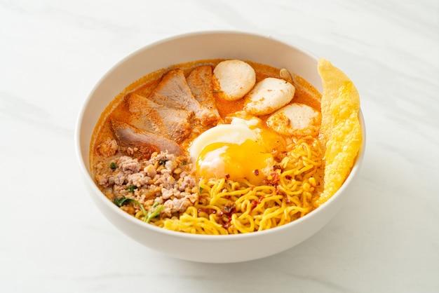 Macarrão de ovo com carne de porco e almôndega na sopa picante ou macarrão tom yum no estilo asiático