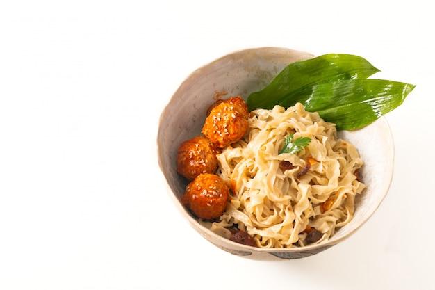 Macarrão de ovo oriental caseiro comida asiática conceito e almôndegas picantes em tigela de cerâmica no fundo branco