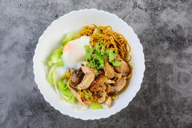 Macarrão de ovo servido seco com frango assado com mel e ovos cozidos (ovos onsen tamago)