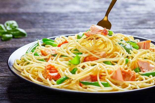 Macarrão de salmão com espaguete, feijão verde, peixe assado e alho com manjericão fresco por cima servido em um prato preto sobre uma mesa de madeira escura, close-up