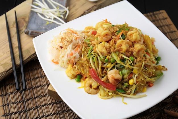 Macarrão de soja com camarão e vegetais em prato branco