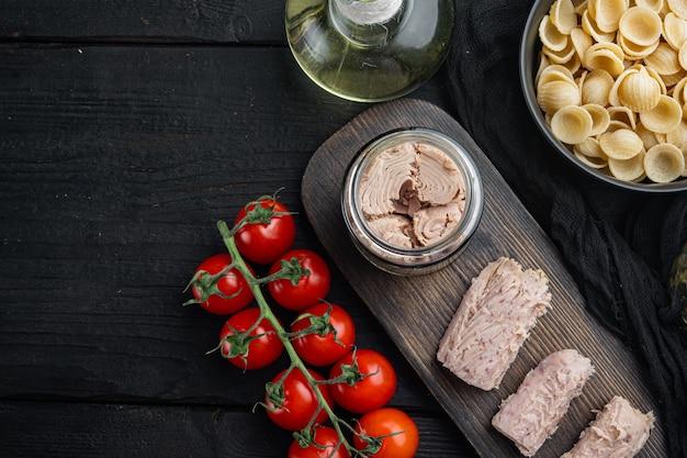 Macarrão de trigo integral com tomates secos e ingredientes de atum, na mesa de madeira preta, vista superior