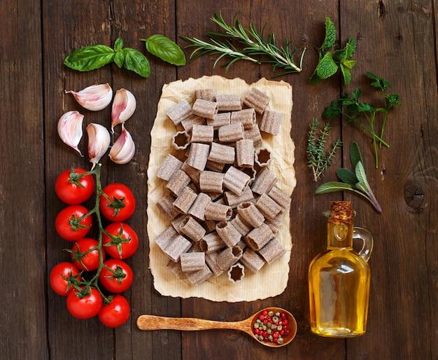 Macarrão de trigo integral, vegetais, ervas e azeite em fundo de madeira