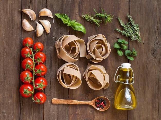 Macarrão de trigo integral, vegetais, ervas e azeite na mesa de madeira