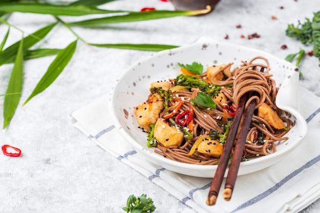 Macarrão de trigo sarraceno japonês yakisoba com frango e vegetais em um fundo claro