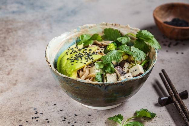 Macarrão de trigo sarraceno - soba com tofu, brócolis, abacate, mudas e coentro, copie o espaço. conceito de comida vegetariana saudável.