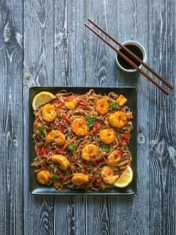 Macarrão de udon de comida asiática com camarão frito, gergelim e pimenta close-up de um prato na mesa de madeira.