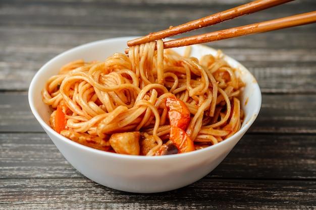 Macarrão de udon wok com frango e legumes em um prato branco sobre fundo de madeira