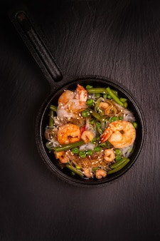 Macarrão de vidro com camarões e legumes verdes em panela de ferro fundido. conceito de comida saudvel.