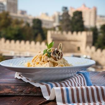 Macarrão de vista lateral com queijo e cogumelos em um prato branco sobre uma mesa de madeira escura com vista cidade